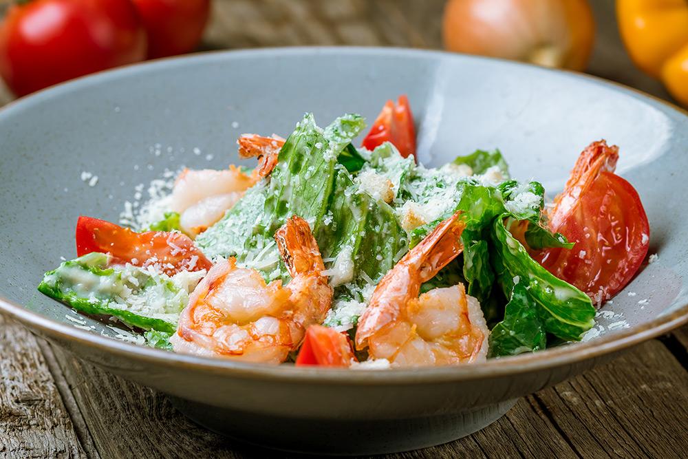 variante della caesar salad con gamberi al posto del pollo