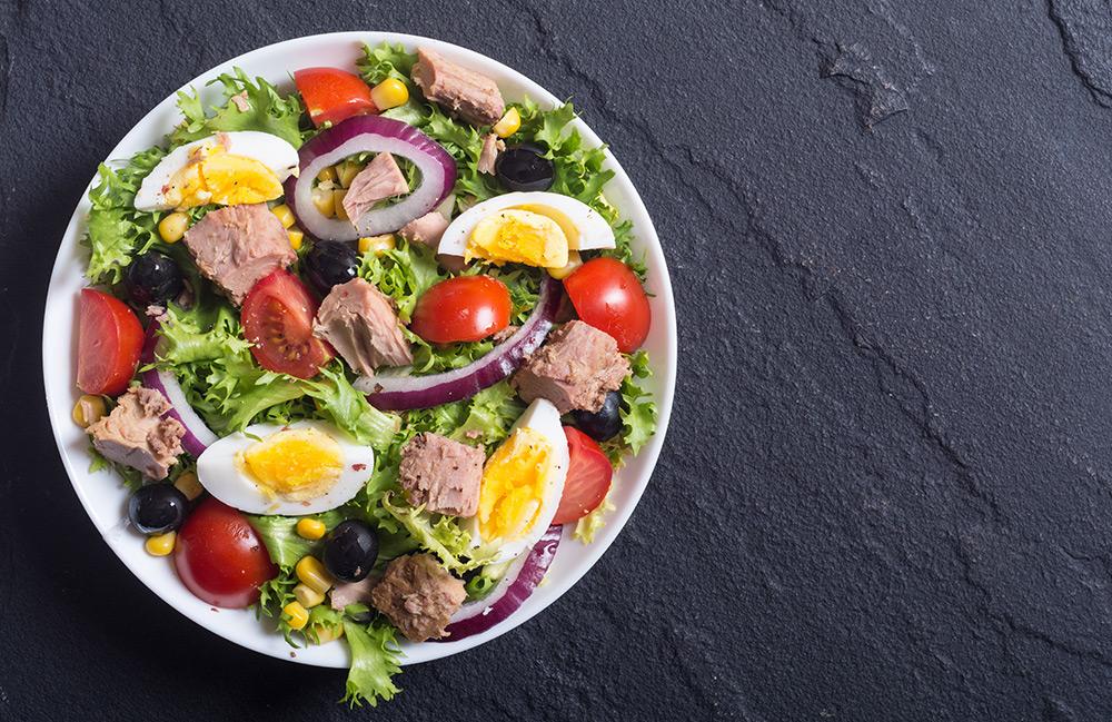 insalata nizzarda con lattuga, tonno, uova, cipolla rossa di tropea, pomodorini