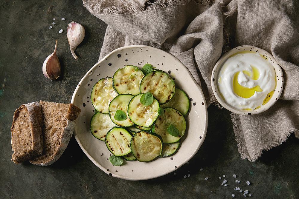 zucchine grigliate con salsa tzatziki, pane ai cereali, olio e basilico