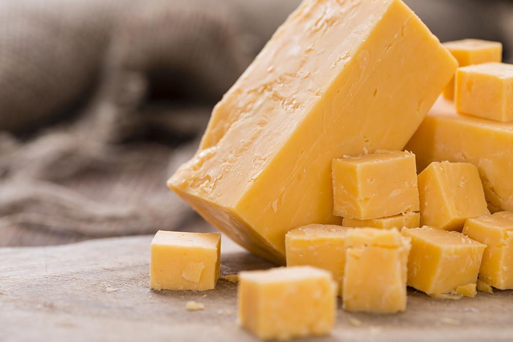 formaggio cheddar su tagliere tagliato a cubetti