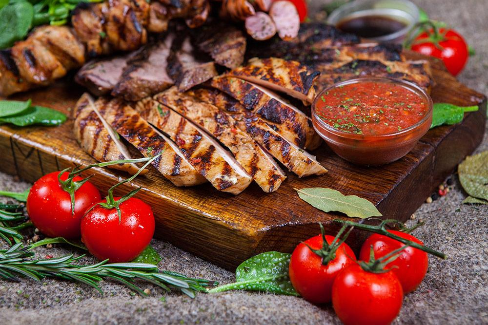 Carne bianca di pollo al barbecue con pomodorini, cipolla e foglie di rosmarino, salvia e basilico